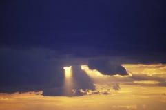 Sun Setting Through Clouds Royalty Free Stock Photos