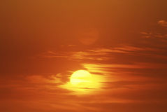 Sun Setting Through Clouds Royalty Free Stock Images