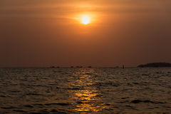 Sun setting a fishing boats head out to sea. Royalty Free Stock Image