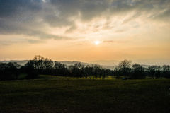Sun setting into fog. Broadway tower view from fish hill looking at the fog filling the Cotswolds Stock Image
