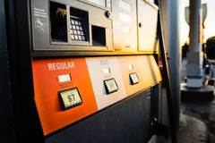 Sun setting on gasoline pump. Gasoline station being illuminated by a warm sunset Stock Images