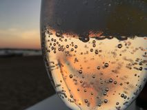 The sun setting through a glass. With a liquid on a table on the beach. Spain royalty free stock image