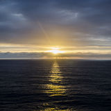 Sun setting on the horizon, reflecting against the surface of the sea. Clouds on the horizon with the sun breaking through and reflecting on the surface of the Stock Photography