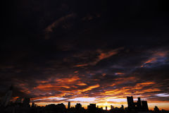 Cloudy Sunset over Urban Skyline Silhouette. The sun is setting, just behind the building in the middle of the skyline silhouette, beneath cloudy fire sky Royalty Free Stock Photo