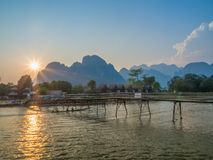 Sun setting on Nam Song River, Laos. Long exposure of pirogues passing under wooden foot bridge over the Nam Song River. Sun setting over impressive limestone stock photo