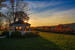 Sun setting in open park area. Sun setting in open park area highlighting trees in fall with gazebo in foreground Royalty Free Stock Image