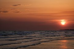 Sun setting over beach Stock Photography