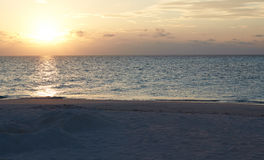 Sun Setting Over Beautiful Deserted Beach Royalty Free Stock Photos