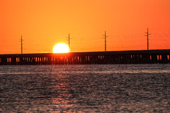 The sun setting over a bridge. The setting of the sun over the ocean is silhouetting a bridge and power lines as it drops behind the bridge creating deep tones Royalty Free Stock Photography