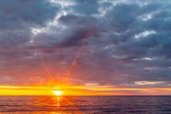 Sun setting over calm ocean waters. Sun setting over calm ocean waters under overcast sky Royalty Free Stock Photography
