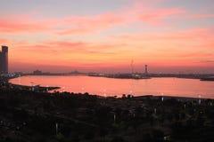 Sun setting over a coastal city landscape Stock Photos