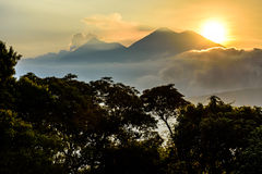 Sun setting over Fuego volcano & Acatenango volcano. Near Spanish colonial town & UNESCO World Heritage Site of Antigua, Guatemala, Central America stock images