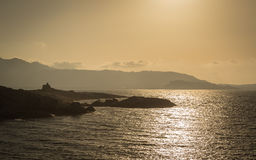 Sun setting over a Genoese tower and Calvi in Corsica Stock Images