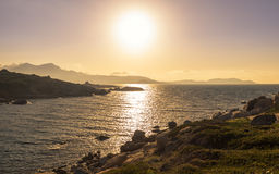 Sun setting over a Genoese tower and Calvi in Corsica Royalty Free Stock Photos