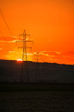 Setting sun over high voltage grid Royalty Free Stock Photos