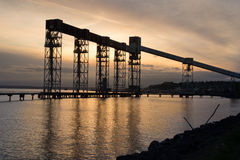 Sun setting over industrial pier Stock Image