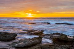 Lajolla Sunset Orange Sky. Sun setting over the La Jolla tide pools. Bright orange sky with sun low on horizon royalty free stock photo