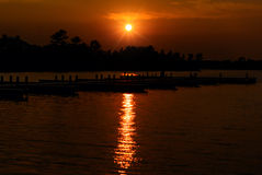 Sun Setting Over a Lake with Docks on the Water Royalty Free Stock Photos