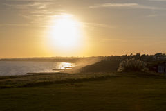 Sun setting over land and sea Stock Photos