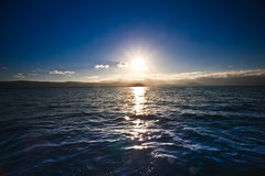 Sun setting over the ocean. Casting a golden pathway over the surface of the water Royalty Free Stock Image
