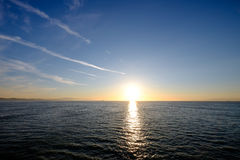 Sun setting over the ocean. Horizon with ships and mountains in the distance Stock Image