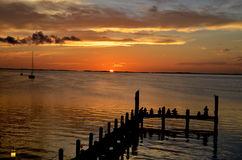 Sun setting over pier at Key Largo. Golden sun rippling over ocean in Florida stock photos