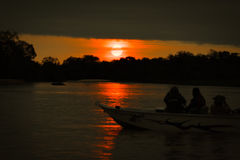 Sun setting over silhouetted boat on river Stock Photo