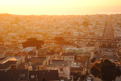 Sun setting over urban roof tops Royalty Free Stock Images