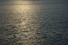 Sun setting over warm water stock image