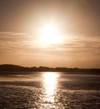 Sun setting over water. With bright colours and reflections Royalty Free Stock Images