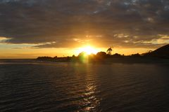 Sun setting on pier in Malibu royalty free stock photography