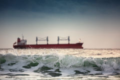 Sun setting at the sea with sailing cargo ship Stock Images