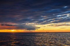 Sun setting at the sea with sailing cargo ship, scenic view Royalty Free Stock Images
