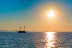 Sun setting at the sea with sailing ship Royalty Free Stock Photos
