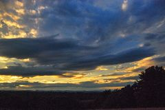 Sun setting in a storm cloud covered late summer sky. Dark, blue, white,sky, clouds Stock Photography