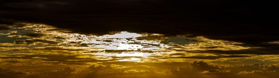 Sun setting in stormy setting panorama. The sun begins to drop to the horizon begin the texture of golden soft lit storm clouds royalty free stock photos