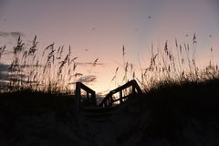 The sun setting in the west shines its light on the beach boardwalk entrance stock photos