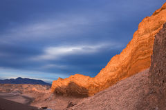 The sun is setting wonderfully on rocky cliffs in moon valley in the atacama desert while overcast by a stormy sky Royalty Free Stock Image