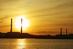 Sun settings behind power pipes Stock Image