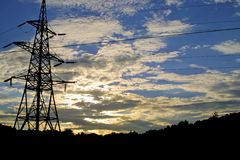 Sun settings behind pylon Royalty Free Stock Photos