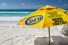 Sun shade on Accra Beach, Barbados. Yellow Carib beer sun shade on the white sands of Accra Beach on the south coast of Barbados. Carib is a beer brewed by Carib royalty free stock photos