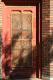 Sun and shade on old brick building and ornate door Stock Photo