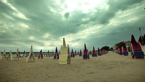 Sun shades and deckchairs in perspective. Sun shades and deckchairs arranged in lines on the sandy beach stock footage