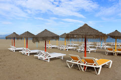 Sun shades and loungers in Torremolinos, Spain. Sun shades and empty loungers in the sandy beach of Torremolinos, Costa Del Sol, Andalusia, Spain in late stock image
