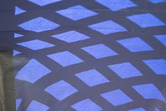 Abstract angles blue distortion on fabric. Sun and shadows create abstract blue lines and angles on fabric outdoors. Background, imperfections, angles royalty free stock photos