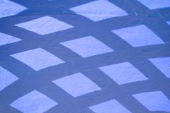 Abstract angles blue distortion on fabric. Sun and shadows create abstract blue lines and angles on fabric outdoors. Background, imperfections, shades of blue royalty free stock photos