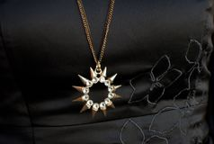 Sun shaped necklace. Sun shaped piece of necklace on a black texture Royalty Free Stock Images