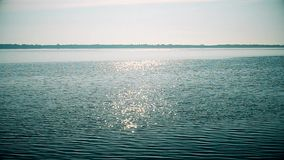 Sun shin sparkles on water surface of river or lake stock video footage