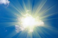 Sun shine from behind cloud. On blue sky Stock Image