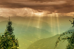 Sun shine from Cloud burst - Sikkim , India. Sun rays coming out of cloud burst - at Rabangla, Sikkim, India. Trees in foreground and Himalayan mountains in Stock Photo